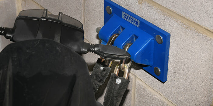 Motor Scooter with security chain fitted to ground anchor fixed to wall