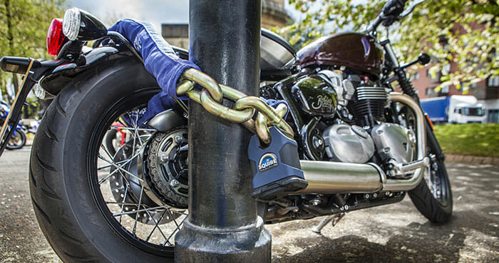 Motorbike with security chain and padlock fixed to lamppost to stop thieves