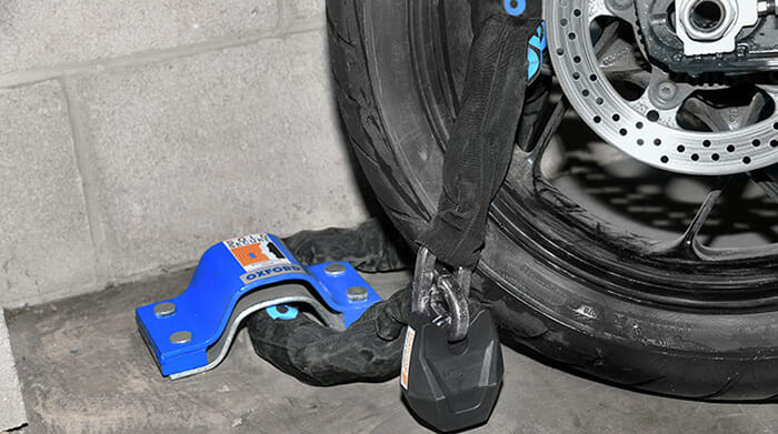 Motorcycle wheel with security chain and padlock fixed to ground anchor on floor